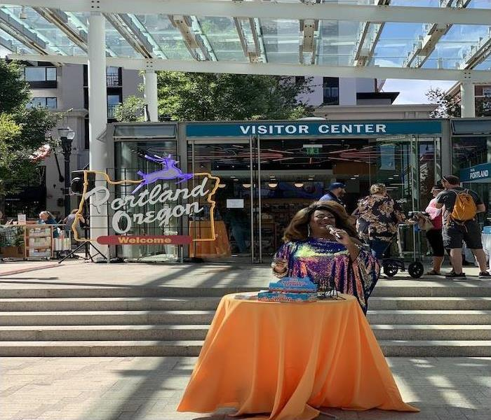 Poison Waters calling Bingo in front of Travel Portland's new location