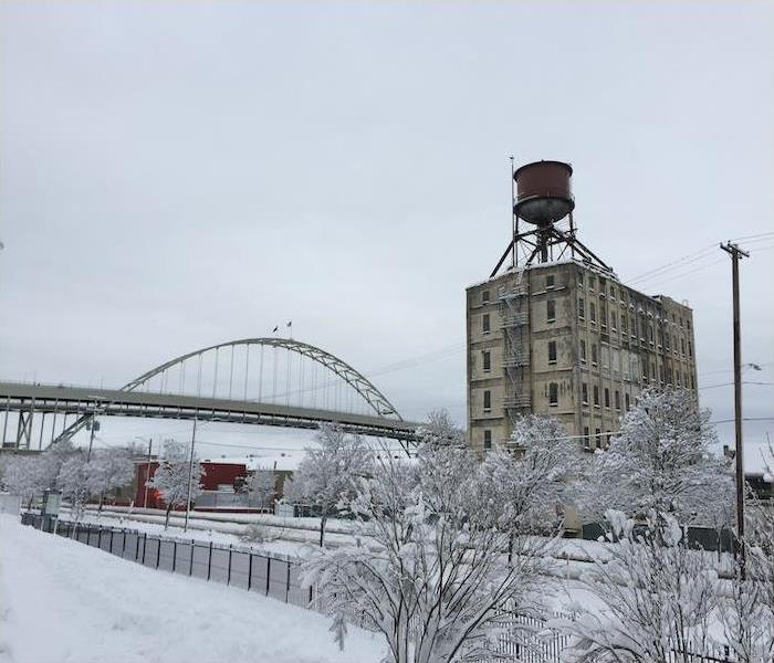 Portland city with bridge and water tower covered in snow.