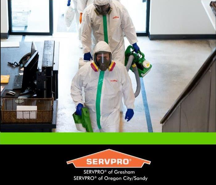 SERVPRO team in PPE walking into an office
